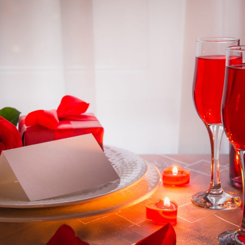 Festive or romantic dinner with red rose and champagne. Romantic invitation. Valentine day. Table reserved.